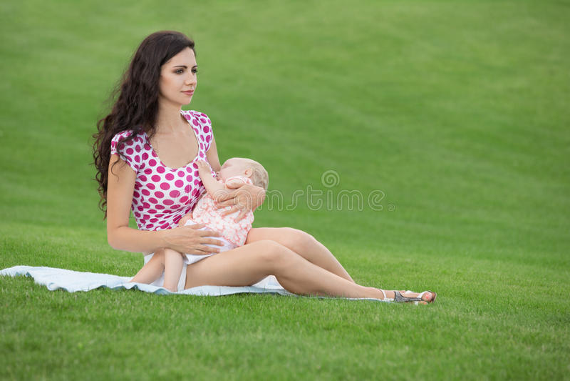 哺乳她的婴孩的妇女户外 免版税库存照片