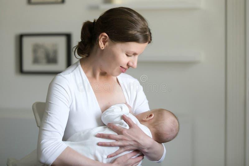 哺乳孩子的一名年轻可爱的妇女的画象 图库摄影