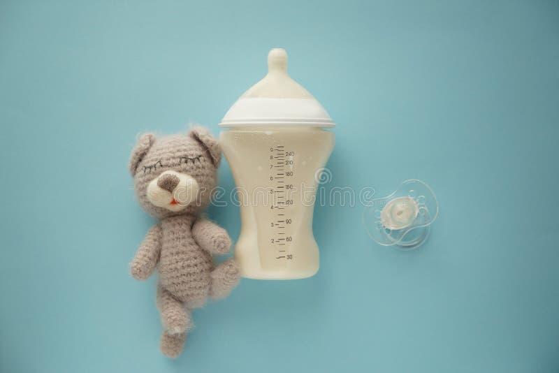 哺乳瓶与安慰者和玩具的奶粉在颜色背景 库存图片