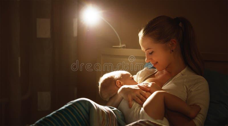 哺乳 在床黑暗夜照顾哺养的婴孩乳房 免版税库存照片