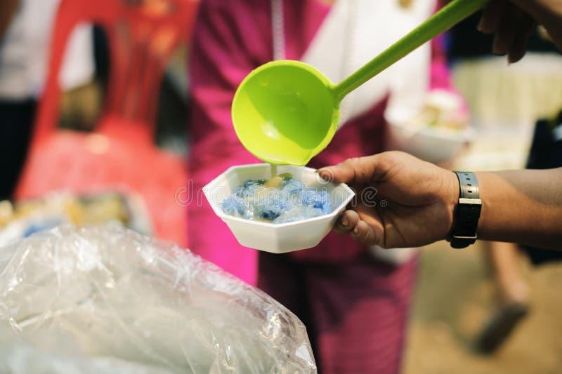 哺养帮助的贫穷的社会问题:哺养饥饿的志愿者在社会:捐赠食物的概念对贫寒 免版税图库摄影