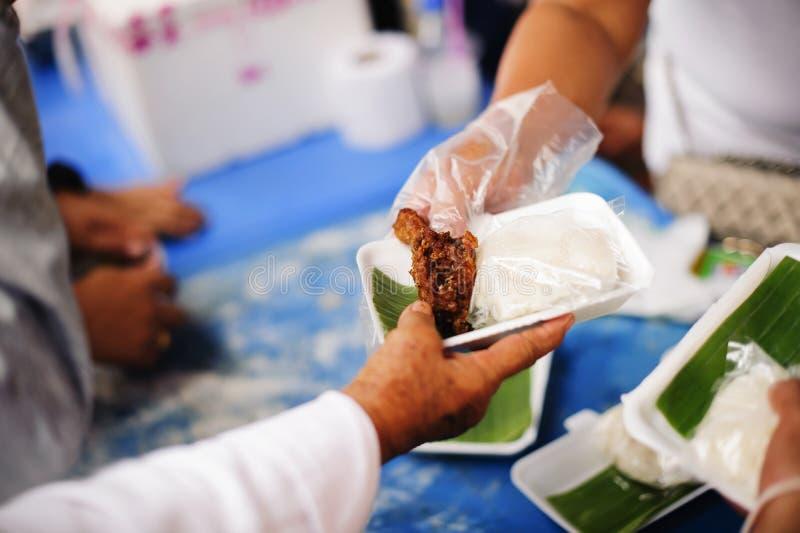 哺养帮助的贫穷的社会问题:哺养饥饿的志愿者在社会:捐赠食物的概念对贫寒 免版税库存照片
