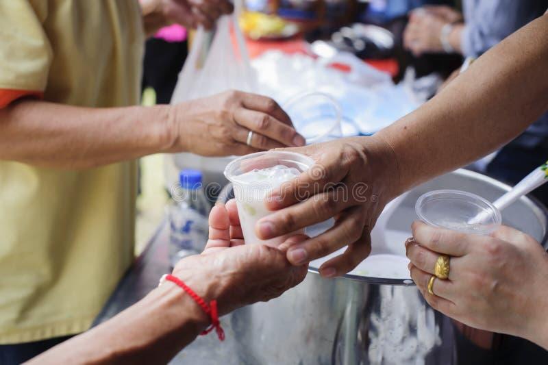 哺养的概念:贫寒分享从更加亲切的社会的食物解除饥饿:可怜的人民的社会概念 图库摄影