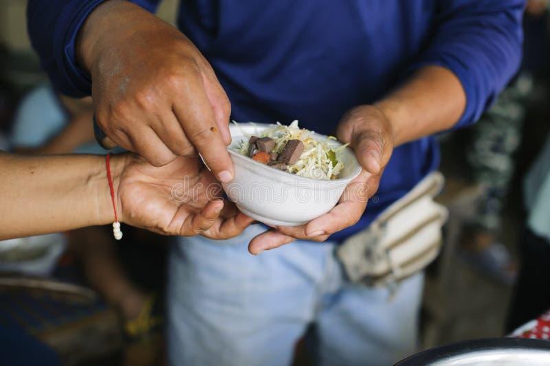 哺养的概念:贫寒分享从更加亲切的社会的食物解除饥饿:可怜的人民的社会概念 库存图片