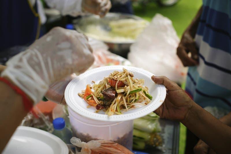 哺养的概念:贫寒分享从更加亲切的社会的食物解除饥饿:可怜的人民的社会概念 免版税库存图片