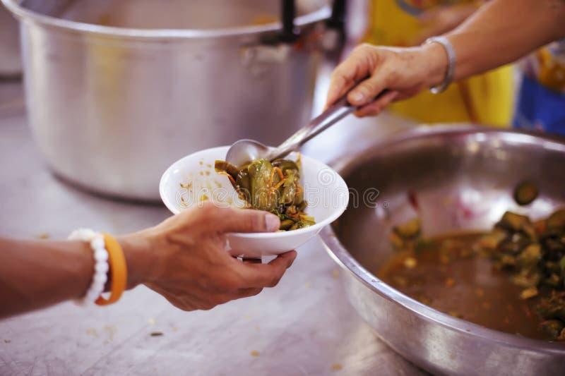 哺养饥饿的志愿者在社会:捐赠食物的概念对社会的贫寒 库存照片