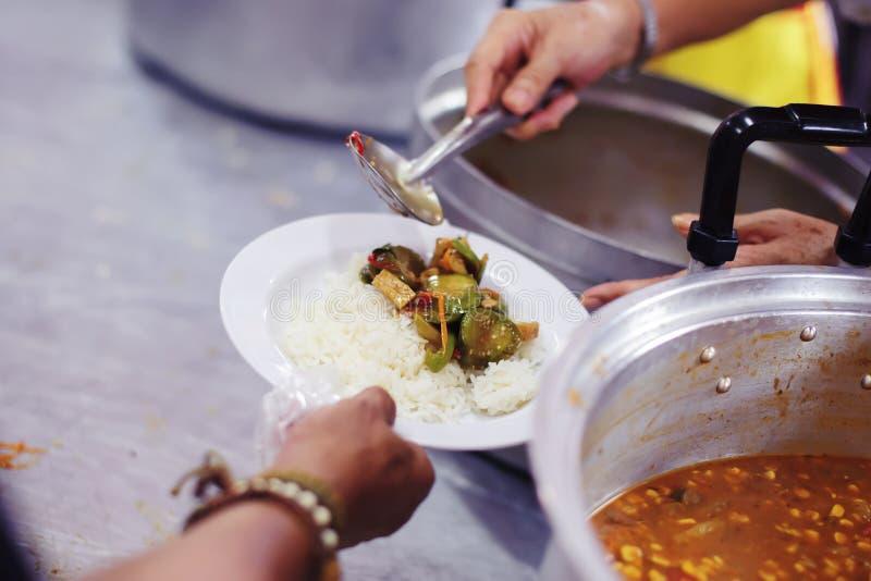 哺养饥饿的志愿者在社会:捐赠食物的概念对社会的贫寒 免版税库存图片
