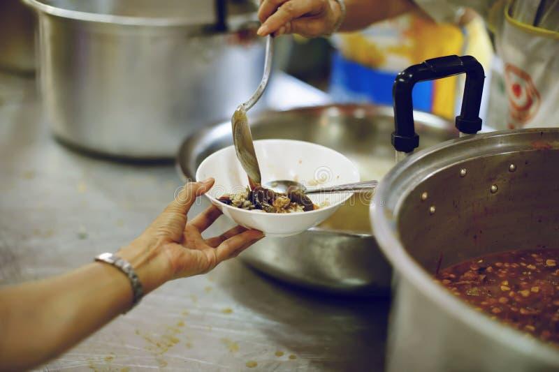 哺养饥饿的志愿者在社会:捐赠食物的概念对社会的贫寒 免版税库存照片