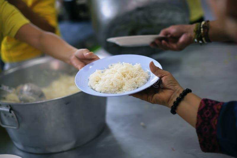 哺养饥饿的志愿者在社会:捐赠食物的概念对社会的贫寒 图库摄影