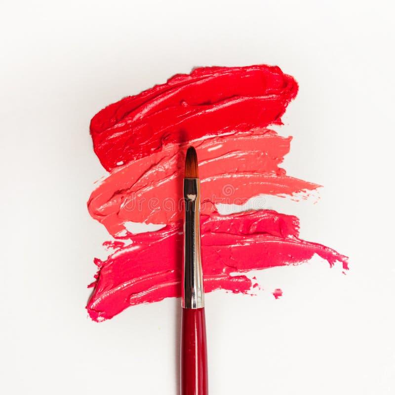 唇膏和唇彩、不同的树荫下落和冲程与刷子的应用和阴影的 库存图片