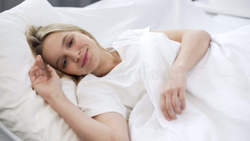 唤醒了十几岁的女孩微笑,满意对舒适的枕头,购买 免版税库存照片