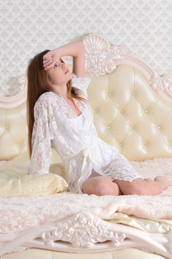 唤醒在床上的年轻女人画象 库存图片