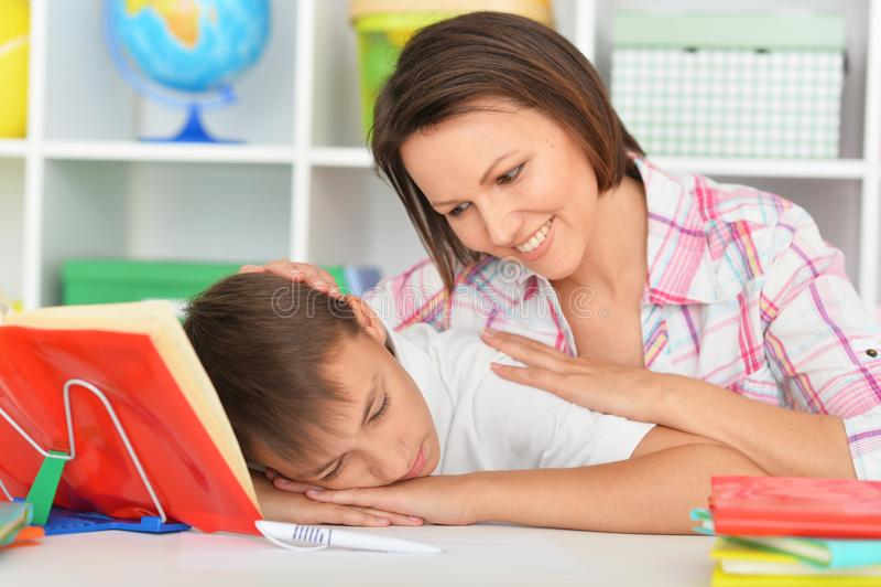 唤醒她的儿子的年轻母亲 免版税库存照片