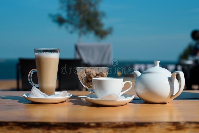 唤醒的概念 套拿铁杯子、茶和一个茶壶用在夏天大阳台的蔗糖 库存图片