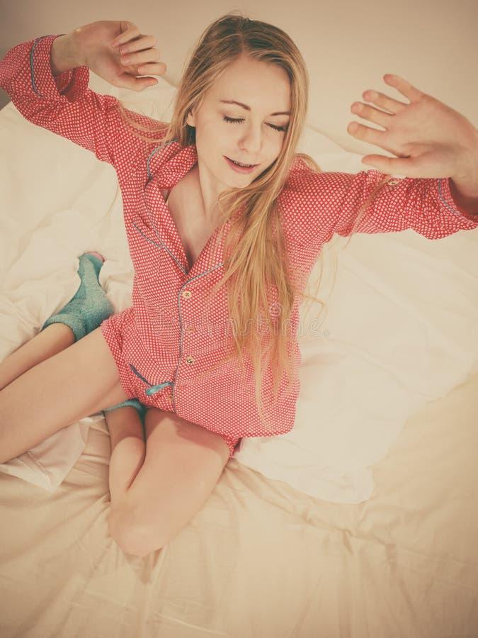 唤醒舒展身体的妇女在睡觉以后 图库摄影