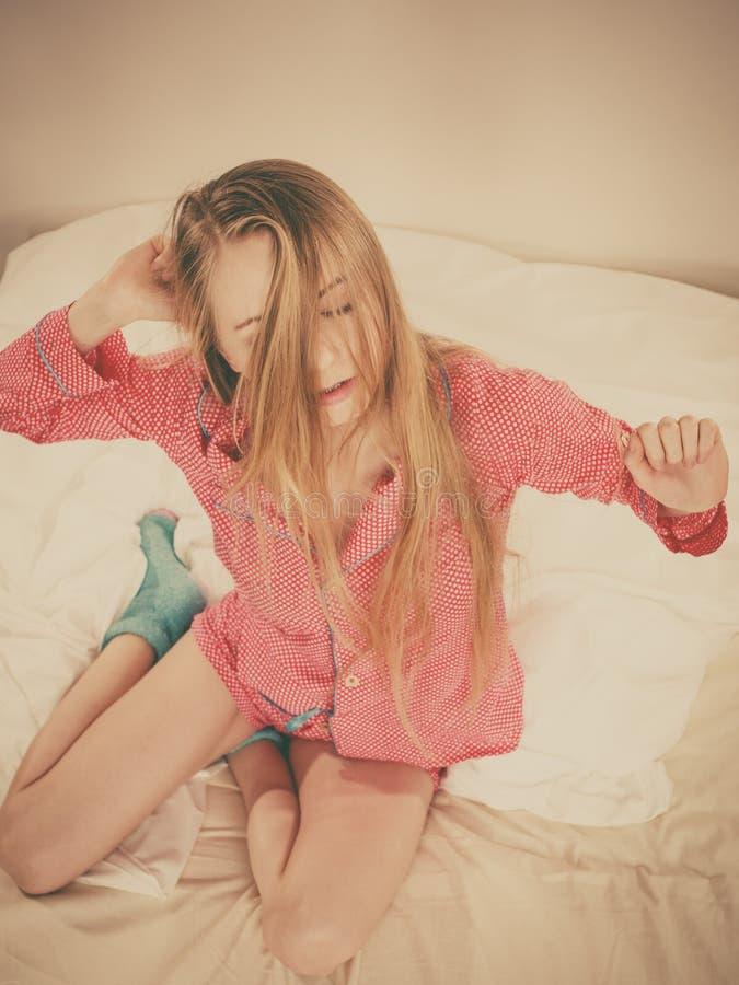 唤醒舒展身体的妇女在睡觉以后 免版税库存照片