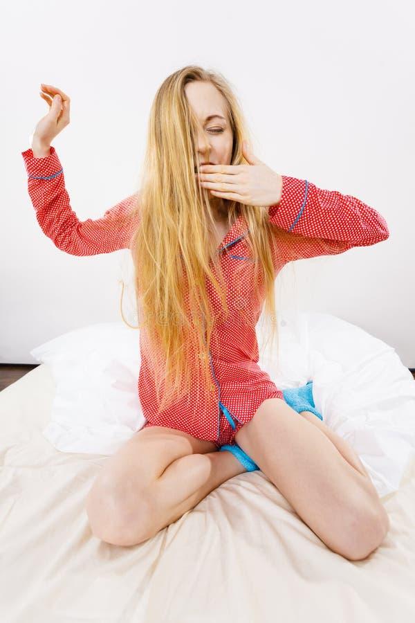 唤醒舒展身体的妇女在睡觉以后 库存图片