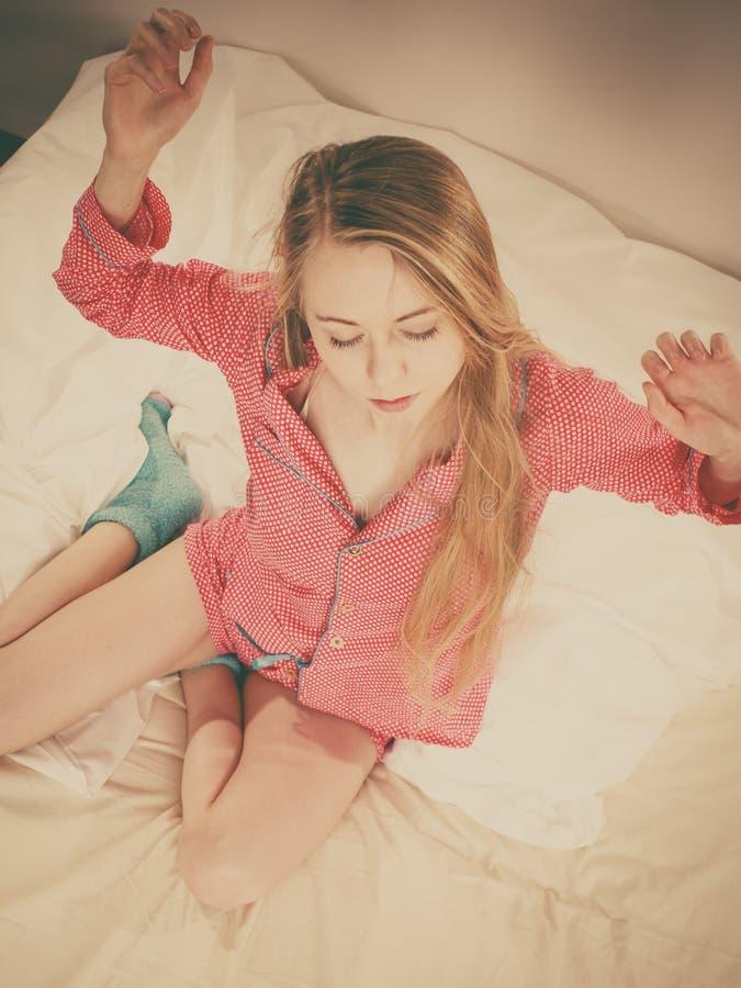 唤醒舒展身体的妇女在睡觉以后 免版税图库摄影
