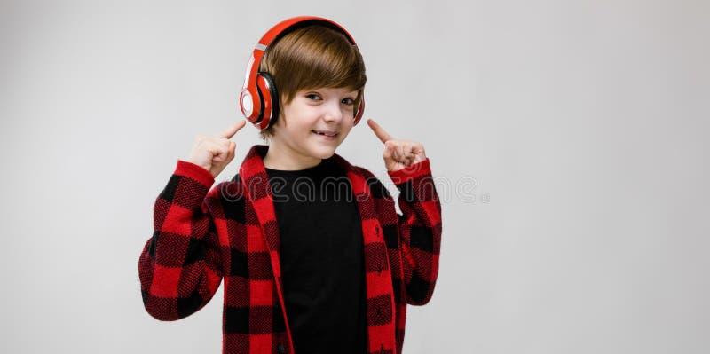 唬弄听到在耳机的音乐的方格的衬衣的逗人喜爱的确信的矮小的白种人男孩在灰色背景 图库摄影
