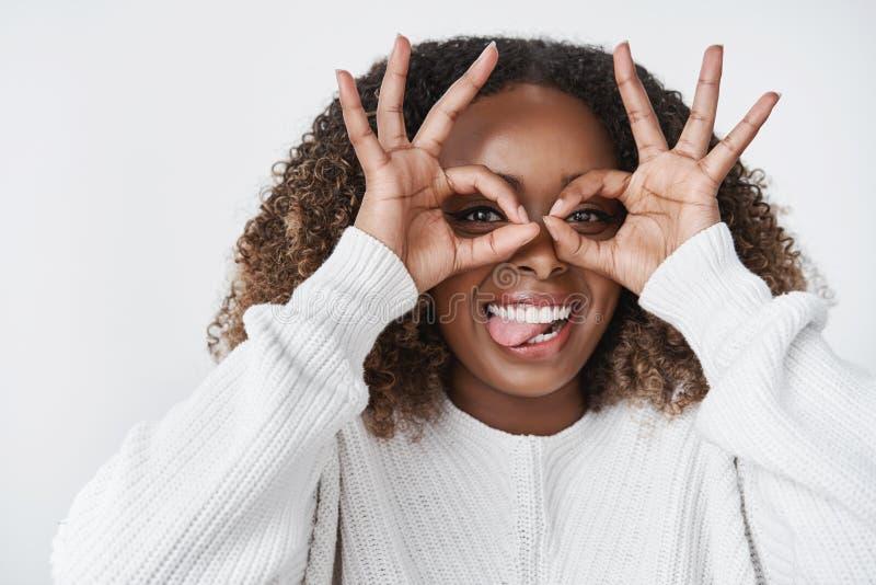唬弄在感觉附近的女孩模仿和做风镜的愉快和快乐的陈列舌头使用手在获得的眼睛乐趣 图库摄影