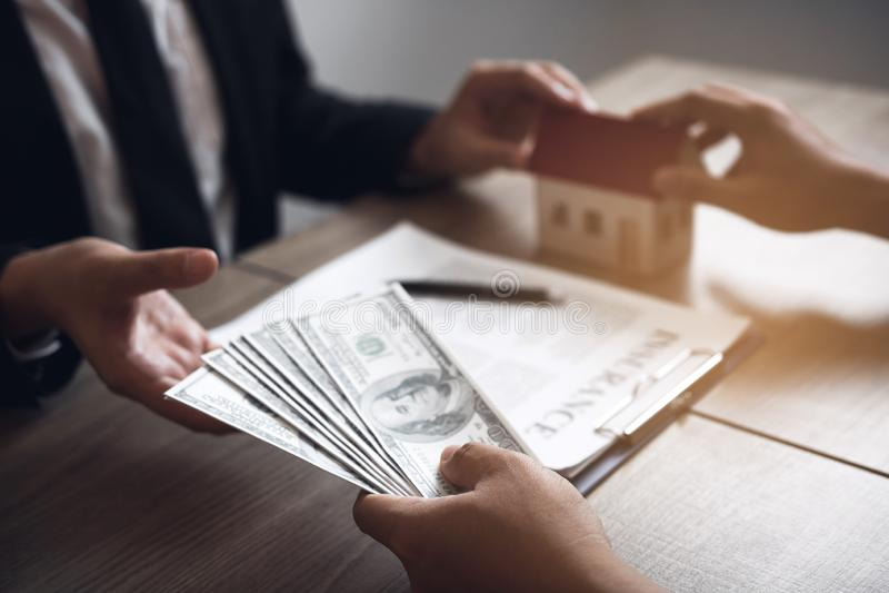 售屋经纪和不动产投资者交换与归档现金的投资者在代理的手 库存图片