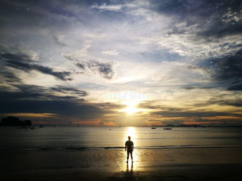 唯一人的树荫和阴影海滩的与日落在甲米府泰国 免版税库存图片