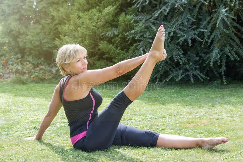唯一平直的腿舒展pos的可爱的资深白肤金发的妇女 库存照片