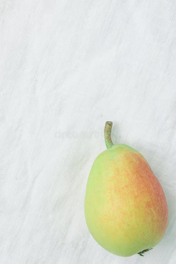 唯一成熟有机梨简单的舱内甲板位置在淡色绿色黄色红颜色的在亚麻制织品 典雅的最低纲领派日本式 免版税库存照片