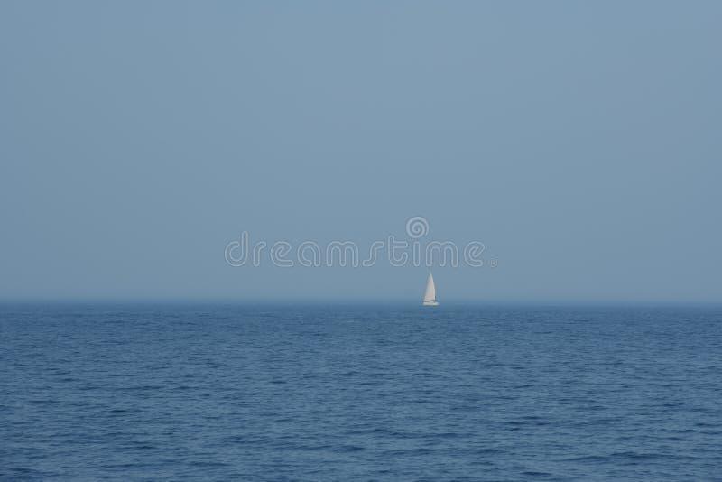 唯一白色风船在蓝色海,简单派 免版税库存图片