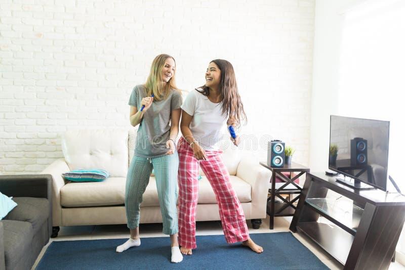 唱卡拉OK演唱和跳舞在客厅的快乐的妇女 免版税库存图片
