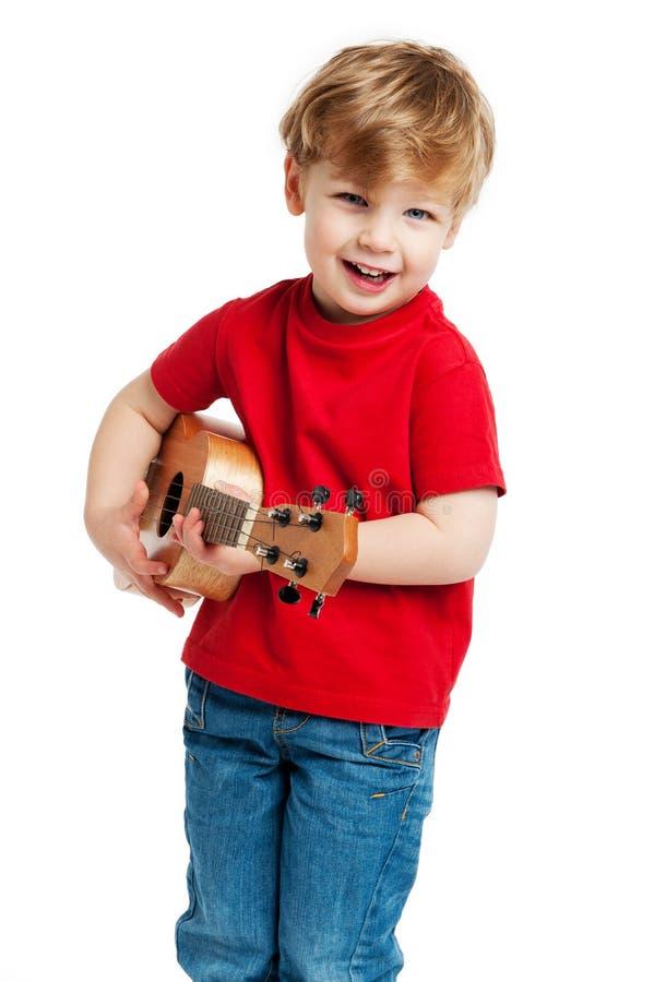 弹尤克里里琴吉他的逗人喜爱的男孩 图库摄影