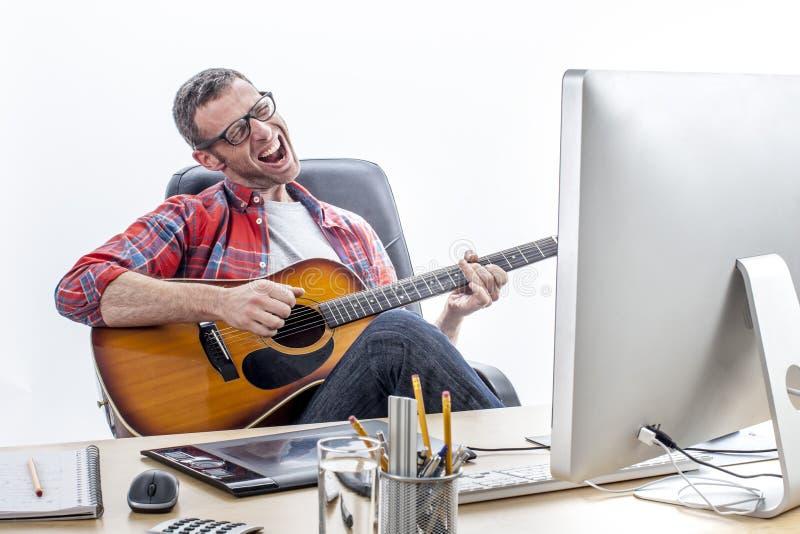 唱和弹吉他的轻松的企业家在家庭办公室书桌 免版税库存图片