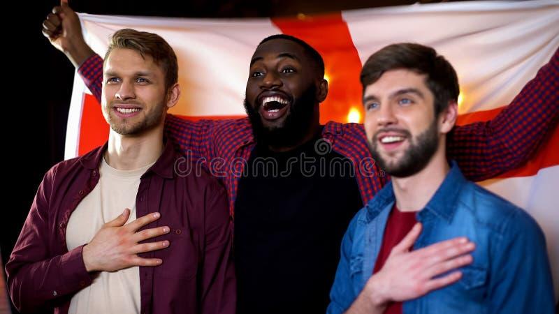 唱国歌,挥动的英国旗子的白种人和黑人男性朋友 库存照片