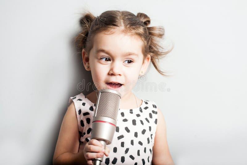 唱在话筒的愉快的逗人喜爱的小女孩一首歌曲 灰色背景 库存照片