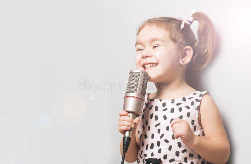 唱在话筒的愉快的逗人喜爱的小女孩一首歌曲 灰色背景 免版税库存照片