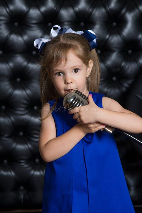 唱在话筒的愉快的逗人喜爱的小女孩一首歌曲 黑色用皮革包盖的背景 库存照片