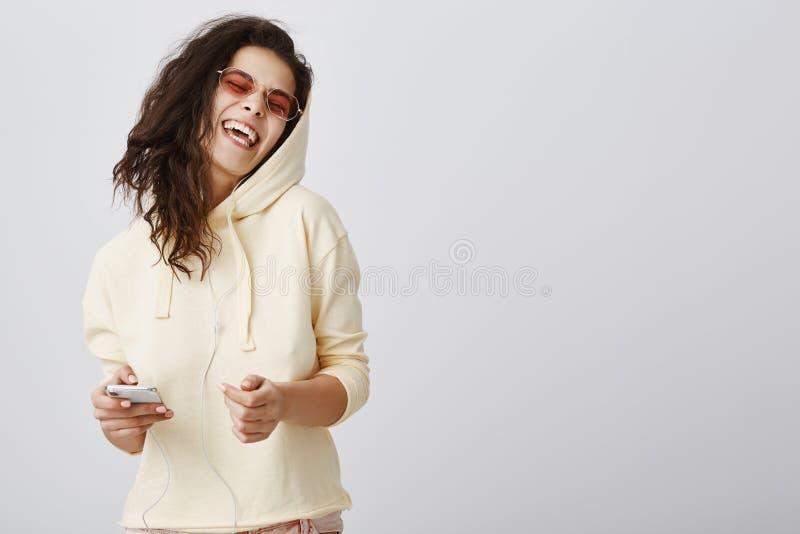 唱她心脏  正面快乐的白种人女孩画象黄色掀动头的有冠乌鸦和时髦的eyewear的 免版税库存图片