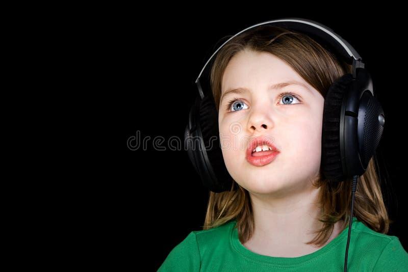 唱年轻人的逗人喜爱的女孩耳机 免版税库存照片