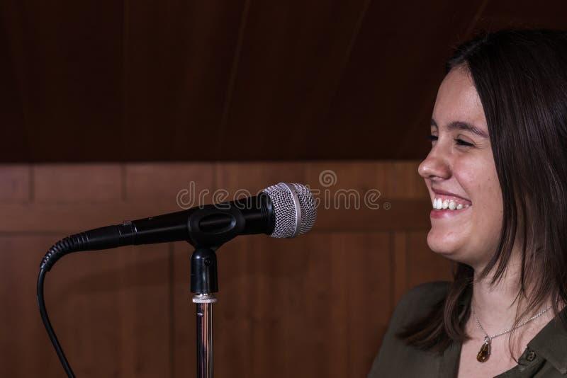唱歌与一个话筒的女孩在音乐演播室 图库摄影