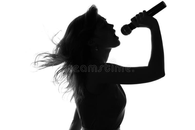 唱歌与一个话筒的妇女的剪影在手上 免版税库存图片