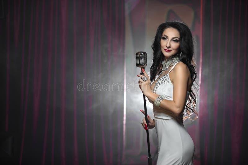 唱歌与减速火箭的话筒的美丽的魅力妇女 库存图片