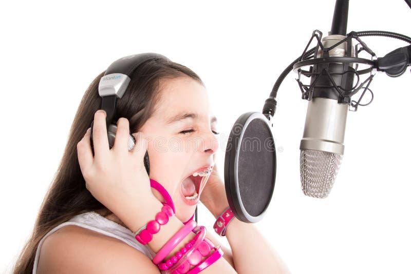 唱歌与在空白背景的话筒的女孩 免版税库存图片