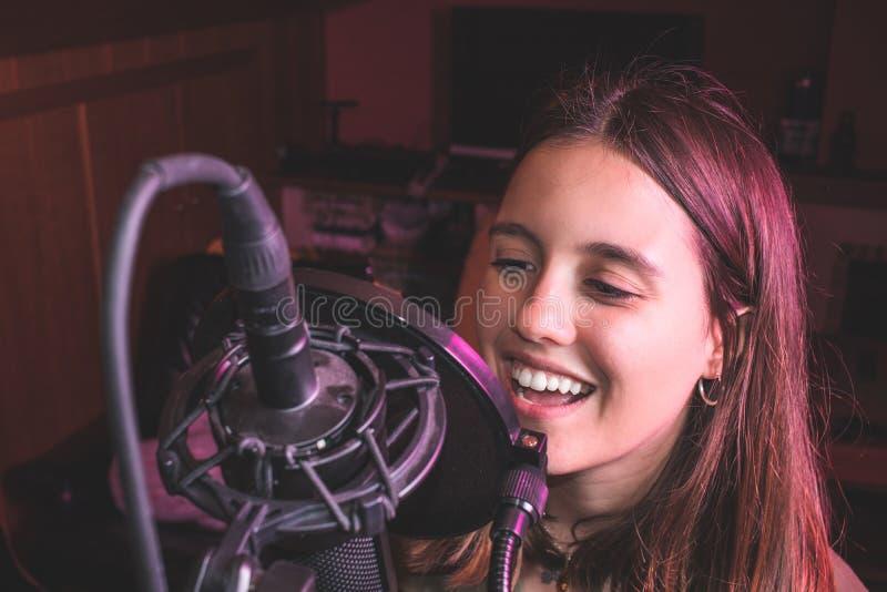 唱歌与话筒的唱歌的女孩 免版税库存图片