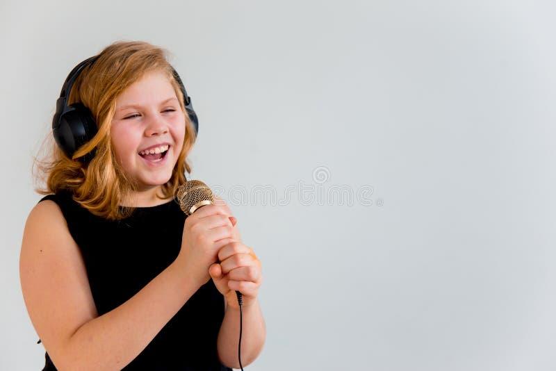 唱歌与话筒的女孩 免版税库存照片