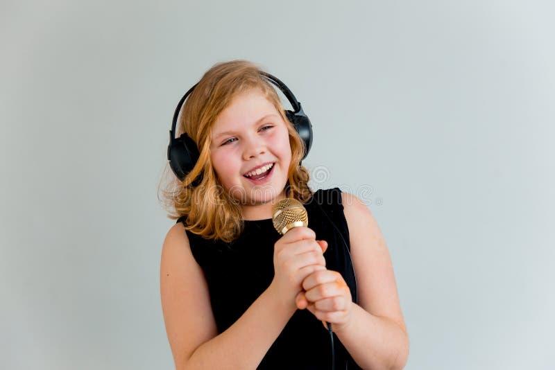 唱歌与话筒的女孩 免版税图库摄影