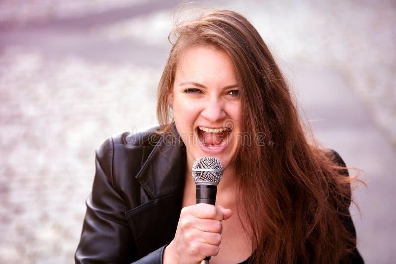 唱歌与话筒的年轻深色的妇女户外 免版税库存照片