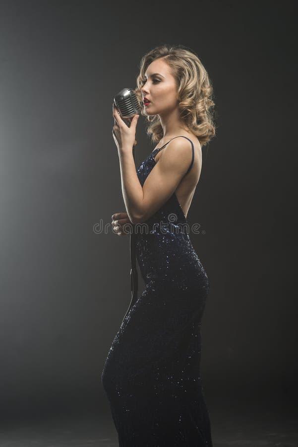 唱歌与银色减速火箭的话筒的性感的女孩歌手 免版税库存照片