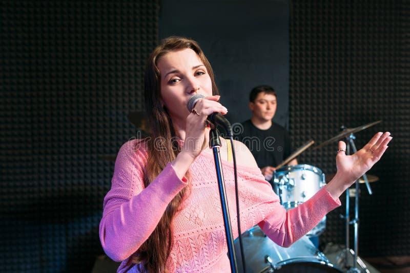 唱歌入话筒的女性独奏者 免版税图库摄影