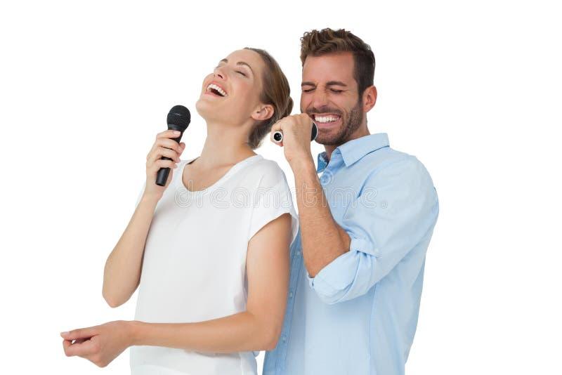 唱歌入话筒的快乐的夫妇 图库摄影