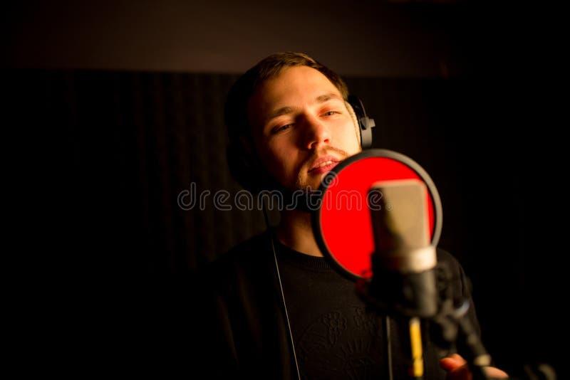 唱歌入话筒的男性歌唱者在录音室 创造新的流行歌曲 图库摄影